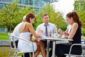 Group of business people drinking coffee outdoors in a coffee shop